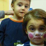 Foto: kleines Mädchen wird gerade mit Pinsel im Gesicht bemalt. Im Hintegrund schaut ein Junge zu. Beide Blick zum Betrachter.