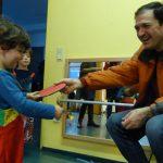 Foto: Kind und erwachsener Mann schäkern lachend und ziehen an der selben Tischtenniskelle. Kind im Hintergrund schaut zu.