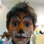 Foto: Porträt eines Junge mit bemaltem Gesicht (Motiv Tieger) und hochgezogener Augenbrauen mit Blick zum Betrachter.