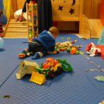 Foto: 3 Kleinkinder spielen mit diversem Spielzeug auf dem Fußboden. Rückenansicht.