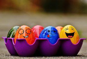 Foto: 6 bunte Eier in einem Eierhalter, davon 3 mit Gesichtern bemalt