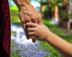 Foto: eine Kinderhand umfasst eine Hand eines Erwachsenen. Im Hintergrund verschwommen ein Weg.