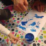 Foto: Tuschezeichnung, Tuschefarbtöpfchen blau und Kinderhand mit Pinsel darin auf einem Tisch mit bunt bepunkteter Tischdecke. Erwachsenenhand will helfen. Draufsicht von oben.