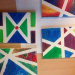 Foto: 4 Tusche-Kinderzeichnungen mit bunten eckigen Motiven auf einem Holztisch. Draufsicht von oben.