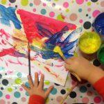 Foto: Tuschezeichnung, Tuschefarbtöpfchen blau, gelb und grün und Kinderhände bzw. -hand mit Pinsel beim zeichnen. Draufsicht von oben.