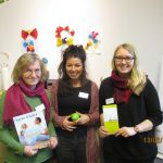 Foto: 3 Frauen mit Blick zum Betrachter halten je Prospekt oder Broschüre oder einen kleinen grünen Ball mit Schriftzug Vista auf Bauchhöhe den Händen. Hintegrund rechts ein Flipchart.