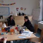 Foto: Frau sitzt rechts an einem Tisch, rechts von ihr sitzt ein junger Mann. Besprechnungssituation. Flipchart im Hintergrund.