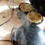 Foto: 2 Waffeleisen dampfen vor sich hin, wobei eines geöffnet ist und 2 fertige Waffelsterne zeigt.