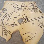 Foto: eine am Rand und in der Mitte ausgefranzte und angebrannte Papierkarte mit Zeichnungen darauf liegt auf Steinfußboden.