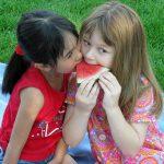 Foto: zwei Mädchen sitzen auf dem Rasen auf einer Decke und beissen gemeinsam in ein stück Melone.