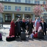 Foto: eine Gruppe Frauen unterschiedlicher Nationalität, teilweise mit Kopftuch, mit Blick zum Betrachter auf dem Bahnhofsvorplatz in Binz. Im Hintergrund rosa blühende Mandelbäume, dahinter das Bahnhofsgebäude mit dem DB-Zeichen.