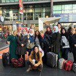 Foto: eine Gruppe Frauen unterschiedlicher Nationalität teilweise mit Kopftuch mit Blick zum Betrachter im Bahnhofsgebäude Berlin Hauptbahnhof. Im Hintergrund Fahrkartenschalter und Geschäfte.