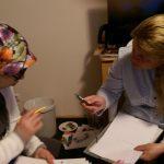 Foto: zwei Frauen, eine davon mit Kopftuch, sitzen sich gegenüber, diskutieren und gestikulieren mit einem Stif in der Hand. Auf ihrem Schoß jeweils Schreibpapiere.