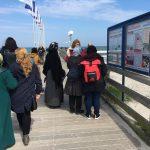 Foto: eine Gruppe Frauen, teilweise mit Kopftuch, am Stand in Rügen vor der Seebrücke mit Blick zum Wasser.