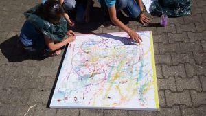 Foto: 3 Kinder hocken vor einer Papierleinwand auf Rahmen die auf Betonsteinplatten liegt und bemlen diese.