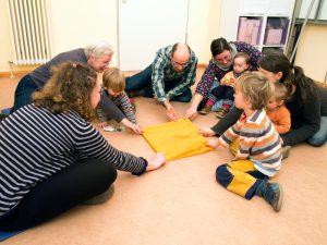 Foto: 5 Eltern sitzen mit ihren Kindern im Kreis auf dem Fußboden und ziehen gemeinsam an allen Ecken eines gelben Tuches in der Mitte von ihnen