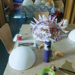 Foto: auf eine Tisch eine weiße Styropor-Halbkugel im Vordergrund, eine bemalte und beklebte Styropor-Halbkugel dahinter. Dazwischen Malzeug.