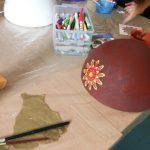 Foto: auf eine Tisch eine weiße Styropor-Halbkugel am linken Rand, dahinter und vorne je eine bemalte Styropor-Halbkugel. Dazwischen Malzeug und kretaiv werkelnde Hände.