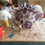 Foto: auf eine Tisch zwei weiße Styropor-Halbkugel im Hintergrund, eine bemalte und beklebte Styropor-Halbkugel mittig. Davor und dazwischen Malzeug.