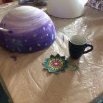 Foto: auf eine Tisch eine blau bemalte Styropor-Halbkugel und eine malende Hand mit Pinsel im Vordergrund, eine weiße Styropor-Halbkugel und Malzeug dahinter.