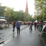 Foto: viele Menschen laufen auf regennasser Strasse zwischen überdachten Ständen. Kirchturmspitze im Hintergrund.