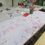 Foto: Tisch diagonal im Bild v.l.u.n.r.o. mit bunt bemalten zusammengeklebten Papierblättern und Malstiften darauf. Tisch mit Prospekten im Hintergrund.