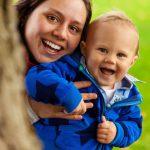 Foto: junge Mutter hält Kleinkind in blauer Jacke unter den Armen auf Kopfhöhe an sich angeschmiegt.