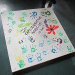 """Foto: weiße Holzplatte mit unterschiedlich farbigen Handabdrücken, dem FZM-Logo und dem Schriftzug """"Familinezentrum Moabit-Ost ist bund!"""""""