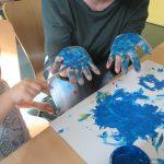 Foto: junge Frau hält ihre Hände mit Innenseite nach oben und Kind bemalt diese mit blauer Farbe