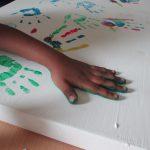 Foto: weiße Holzplatte mit unterschiedlich farbigen Handabdrücken und einer Hand die gerade einen grünen Abdruck macht.