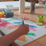 Foto: weißes Blatt auf einem Tisch. Darum diverse Farbtöpfe. Eine Hand malt mit Pinsel auf dem Blat bunte Farbflächen.