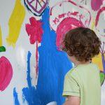 Foto: Kleinkind steht mit dem Rücken zum Betrachter vor einer bunt bemalten Wand und bemalt diese mit Pinsel.