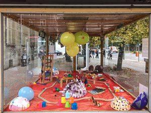 Foto: bunte Bastelobjekte und Spielzeug in einem Glaskasten, der auf einem breiten Gehweg steht.
