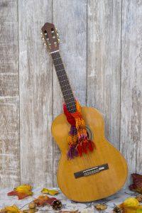 Foto: hochkant stehenden Gitarre mit buntem Schal um den Gitarrenhals lehnt an einer Bretterwand