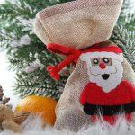 Foto: Leinensack mit Weihnachtsmannbild, daneben Nüsse, Apfelsine und Tannenzapfen, Tannengrün im Hintergrund