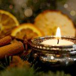 Foto: brennendes Teelicht, Zimt, getrocknete Apfelsinenscheiben auf Tannengrün