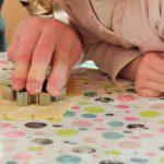 Foto: Kinderhände beim austechen von Plätzen aus Teig mit Sternfigur auf einer bunt bepunkteten Tischdecke