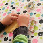 Foto: Kinderhände beimausrollen von Plätzenteig auf einer bunt bepunkteten Tischdecke
