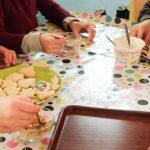 Foto: Kinderhände beim verzieren von Plätzen mit Zuckerguß und bunten Streuseln auf einer bunt bepunkteten Tischdecke