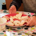 Foto: Kinderhände beim verzieren von Plätzen mit Zuckerguß und bunten Streuseln auf einem Teller auf einer bunt bepunkteten Tischdecke