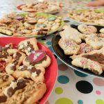 Foto: Plätzchen mit Zuckerguß und bunten Streuseln auf Tellern auf einer bunt bepunkteten Tischdecke
