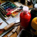 Foto: diverse Malutensilien wie bunte Malstifte, Pinsel, Tuschkasten und Fläschchen mit Farbe