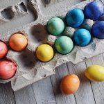 Foto: bunte Ostereier in einer Eierverpackung. 2 Eier liegen daneben. Blick von oben drauf.