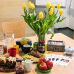 Foto: Tisch mit Kuchen, Äpfeln, Tassen und Gläsern, Teeschachtel und Blumenstauß in Vase
