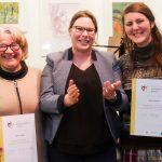 Foto: 3 Frauen mit Blick zum Betrachter. Äußere halten Urkunden vor Bauch, mittlere mit vorgestreckten Händen