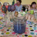 Foto: im Vordergrund Malfarben und Glas mit Pinselwasser und Pinsel sowie bunt bemalte Eier am Holzstil in eine Glas. Im Hintergrund Kinder und eltern beim bemalen von Eiern.
