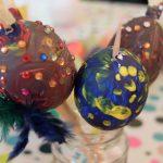 Foto: 3 ausgeblasene Eier, bunt bemalt und teilweise mit bunten Glassteinchen und Federn beklebt, stehen jeweils am Holzstil in einem Glas.