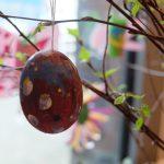 Foto: ein bunt bemaltes ausgeblasenes Ei hängt an Zweigen mit kleinen grünen Blättern vor einer Fensterscheibe im Hintergrund.