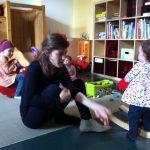 Foto: Frau spielt mit Kind am Schaukelpferd