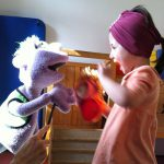Foto: Kind spielt mit einer auf einem Arm gehaltenen Stofffigur